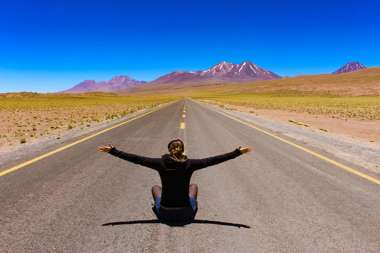 Rear view of carefree woman with arms outstretched sitting on road during sunny day