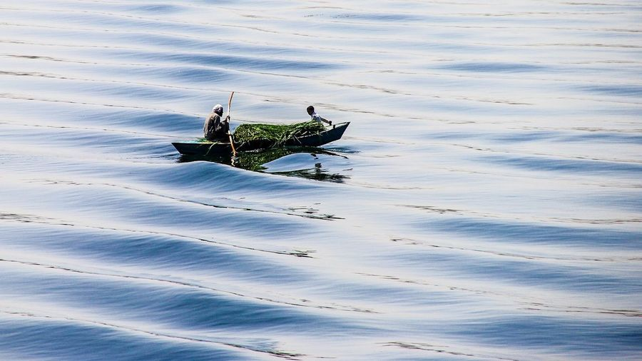 Old Man And Boy In Traditional Fishing Boat On Calm Sea