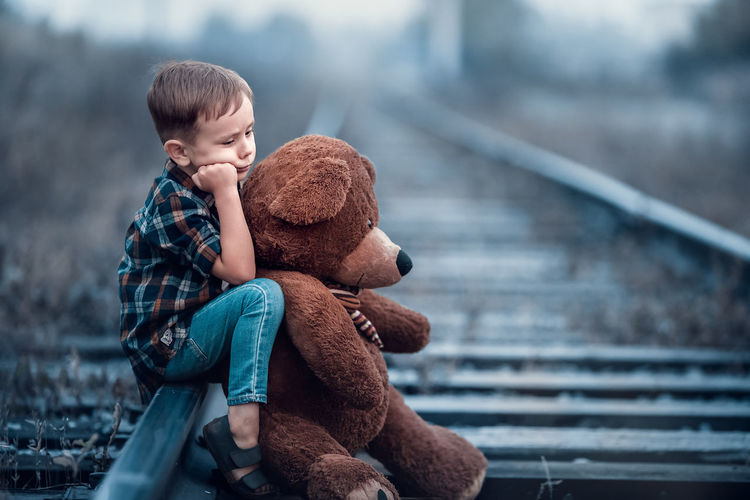 Side view of boy holding teddy bear while sitting on railroad track