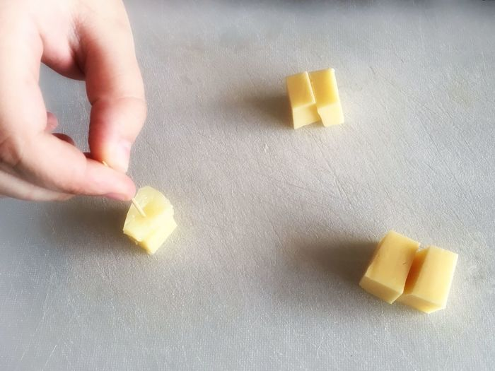 Cropped hand of person holding toothpick on pineapple cube by cheese on table