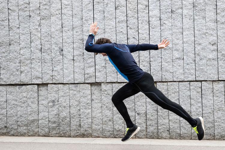 Full length of man climbing on wall