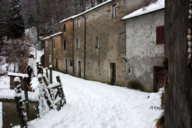 Abandoned village in white snowy mountain peak in reverse in the forest in tuscany