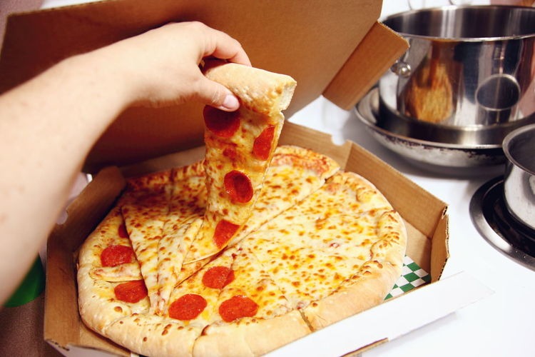 Cropped image of person holding pizza slice from box