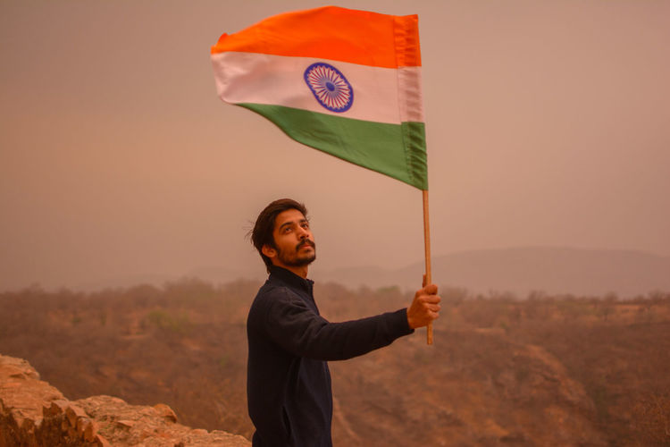 Man holding indian flag on mountain against sky
