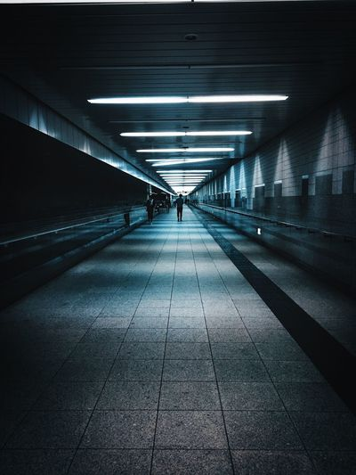 People walking in illuminated underground walkway