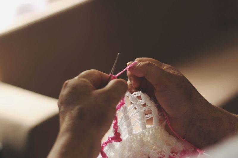 Cropped hands of person weaving wool