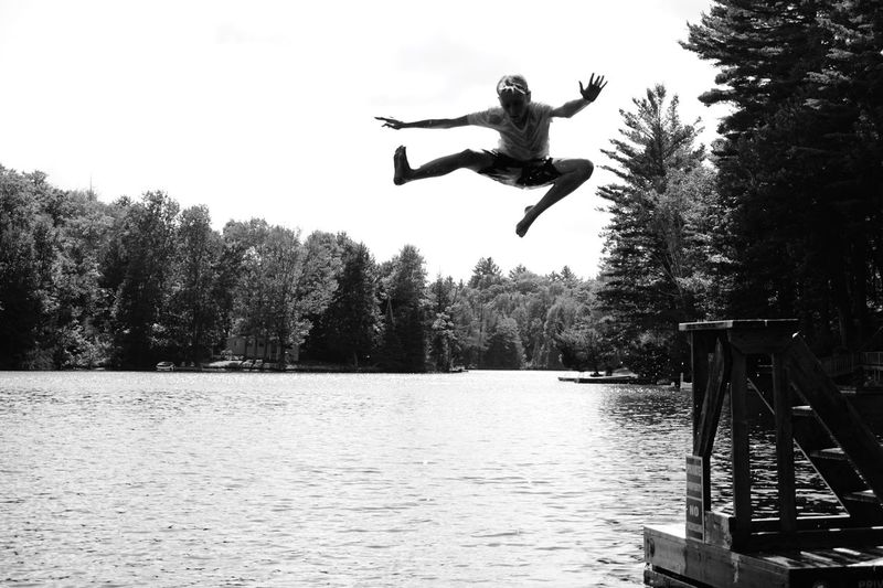 Low angle view of boy jumping in river against clear sky