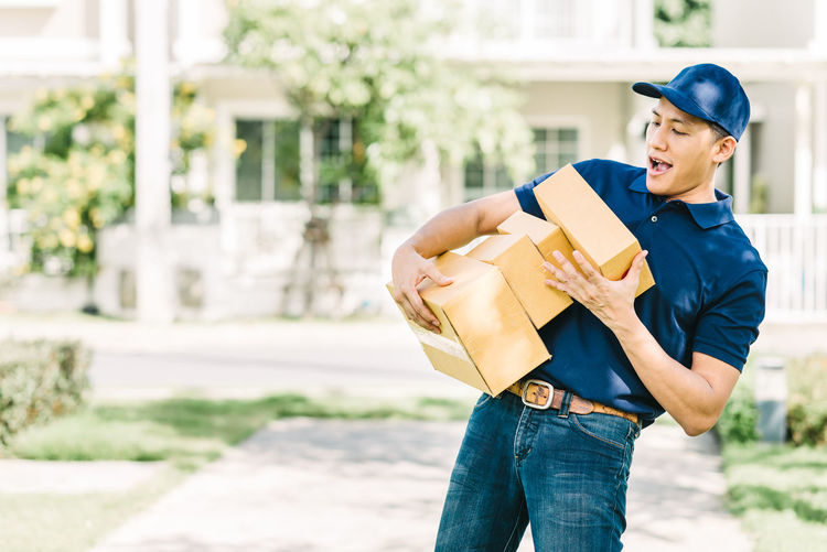 Delivery man holding cardboard boxes while standing outdoors