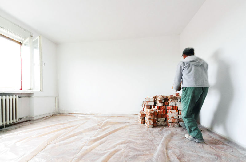 Rear View Of Man Arranging Bricks By Wall At Home During Renovation