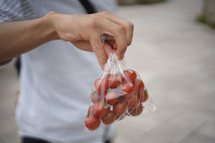 Midsection of man holding cherry tomatoes in plastic bag