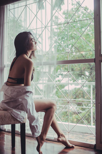 Young woman in lingerie sitting on chair by window at home