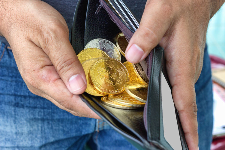 Midsection of man holding bitcoins in wallet