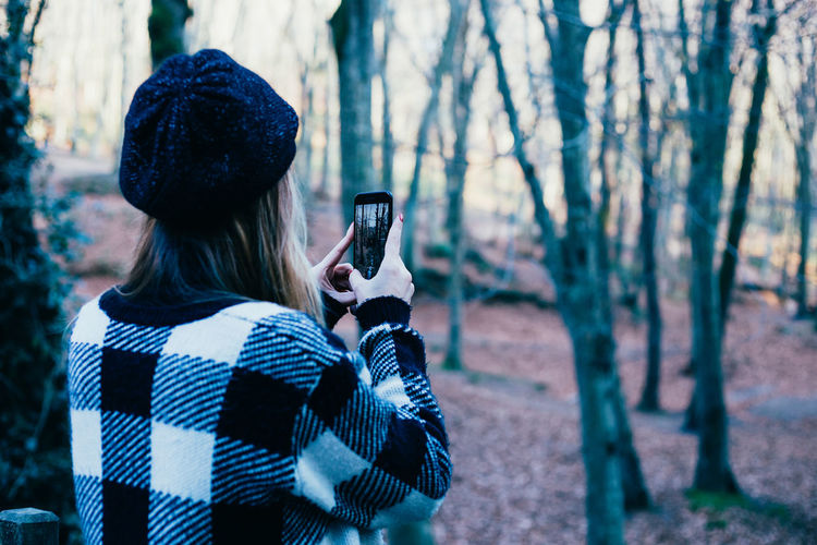 Rear view of woman photographing through mobile phone in forest