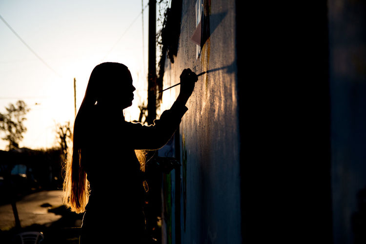 Side view of silhouette woman painting while standing against sky during sunset