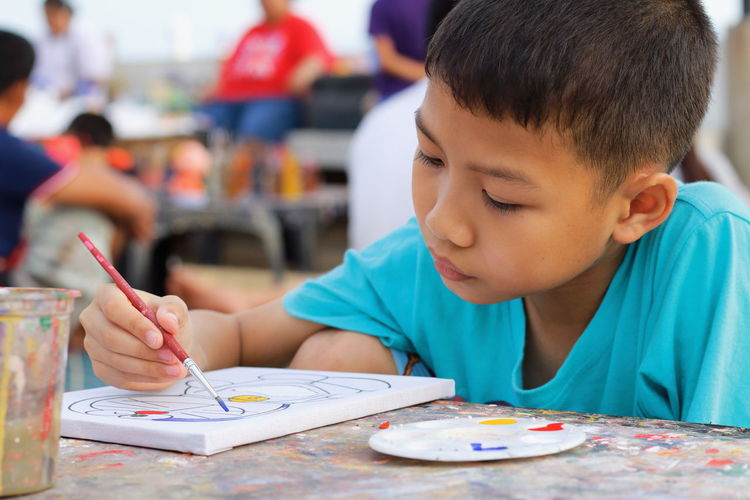 Boy Painting On Paper At Table