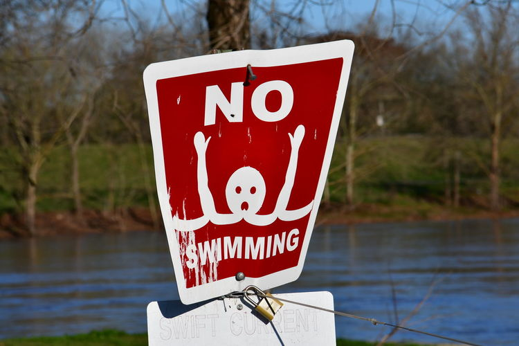 Close-up of warning sign against lake