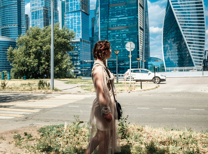 Full length of woman standing against building in city