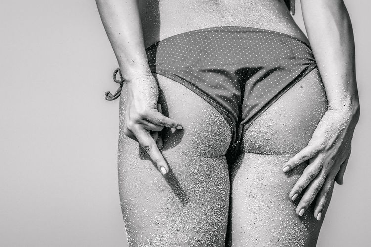 Rear View Midsection Of Woman In Bikini Showing Obscene Gesture