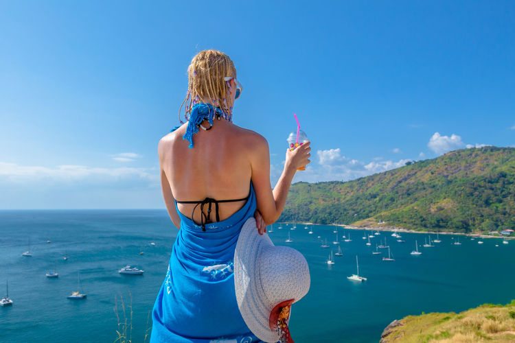 Woman Having Drink While Standing Over Sea Against Sky