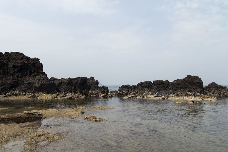 haenyeo who is a female diver picking up sea food near Seongsan Ilchulbong, a dormant volcano in Jeju Island, South Korea Beauty In Nature Cliff Day Dormant Volcano Haenyeo Horizon Over Water JEJU ISLAND  Nature No People Outdoors Rock - Object Rock Formation Scenics Sea Seongsan Ilchulbong Sky Water