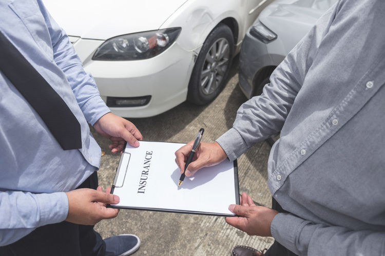 Low section of customer signing application form held by agent