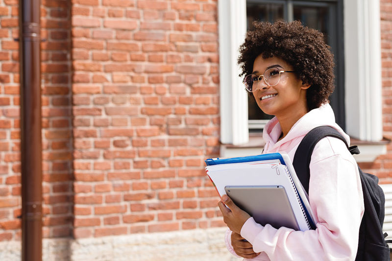 Smiling teenage girl holding books and digital tablet while standing by building