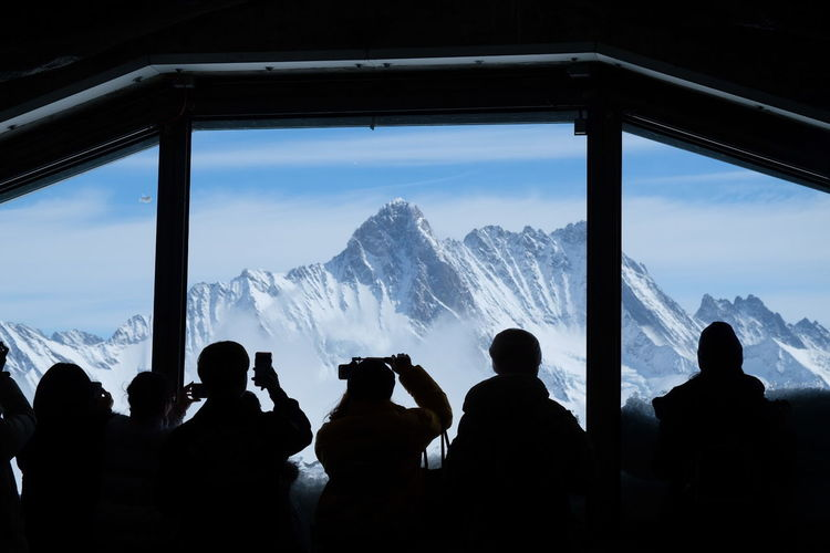 Silhouette people looking at snowcapped mountain through window