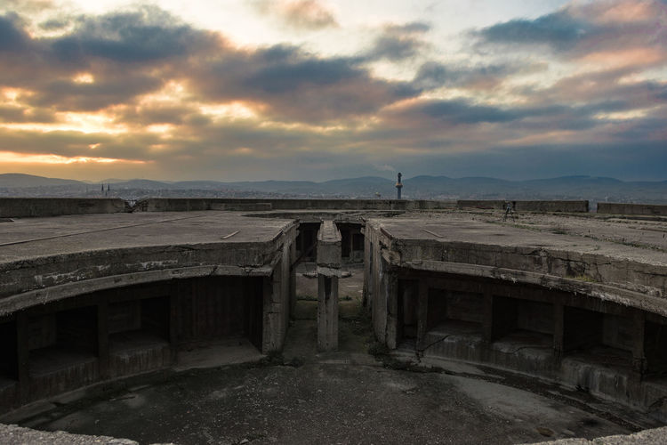 Abandoned built structure against cloudy sky