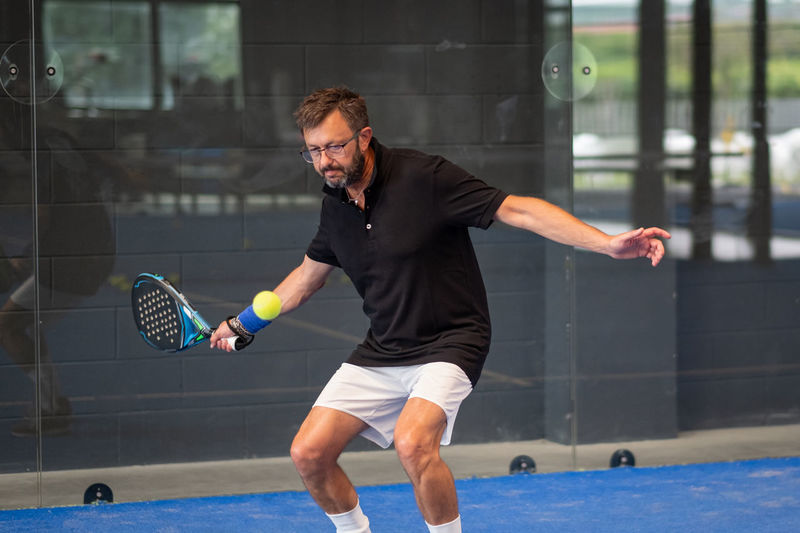Man playing padel in a blue grass padel court indoor - young sporty boy padel player hitting ball