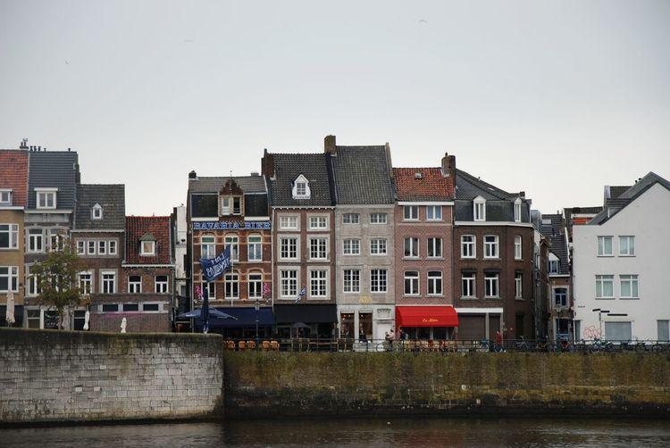 Residential buildings by river against sky