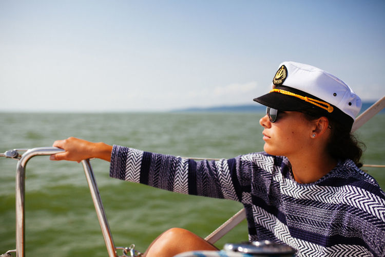 Woman wearing captain hat in boat on sea against sky