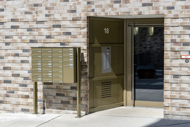 entrance of a building - door with bells and mailboxes Architecture Built Structure Wall - Building Feature Outdoors Brick Window Open Closed Sunlight Brick Wall Shadow Sunny House Door No People Wall Day Building Exterior Entrance Building Mailboxes Entrance Doors