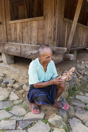 WOLOGAI, INDONESIA - MAY 14: An unidentified man carves next to a traditional house in the traditional village in Wologai, Indonesia on May 14, 2017. Coffee Houses INDONESIA Moni Rice Tourist Travel Tree Art Attraction Authentic Culture Destination East Nusa Tenggara Ethnic Hard Wood House Kelimutu Landmark Sculpture Tourism Traditonal Tribe Village Wologai