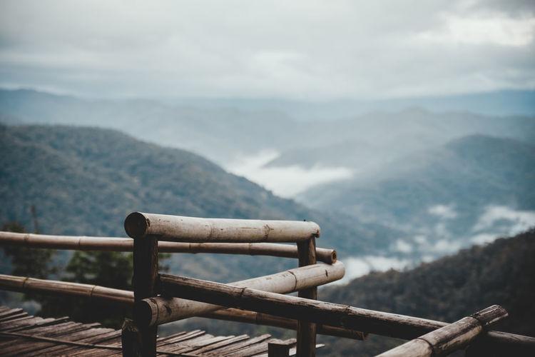 Metallic railing against mountain range against sky