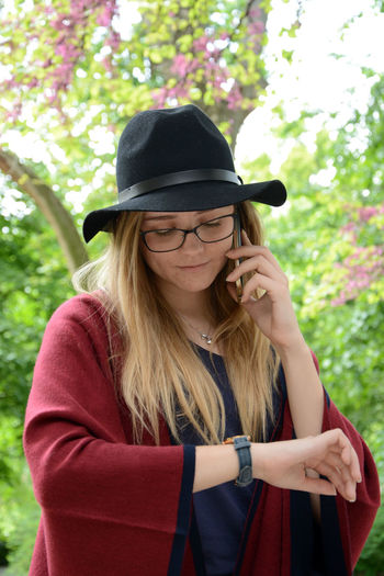 Young Woman Talking On Mobile Phone While Checking Time Against Tree