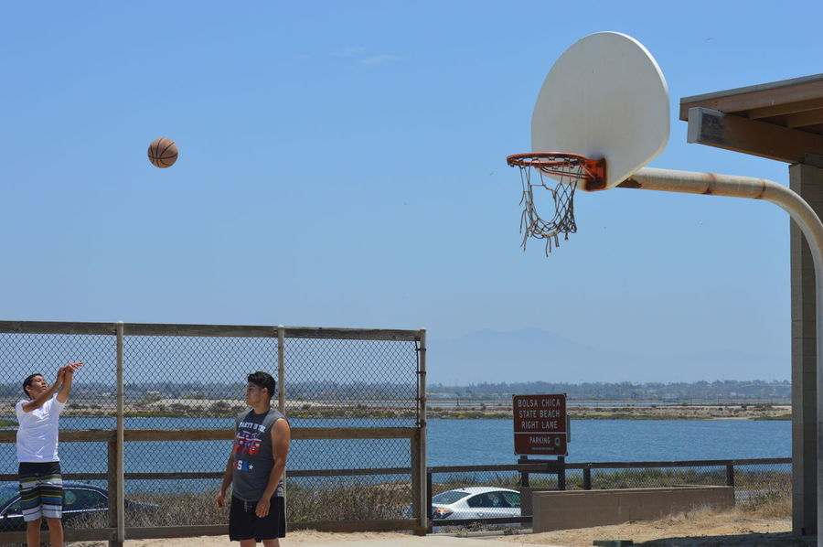 Basketball - Sport Basketball Hoop Beach Beach Volleyball Clear Sky Court Day Leisure Activity Men Mid-air Net - Sports Equipment Outdoors People Playing Real People Sea Sky Sport Sports Team Sportsman Team Sport Water Young Adult