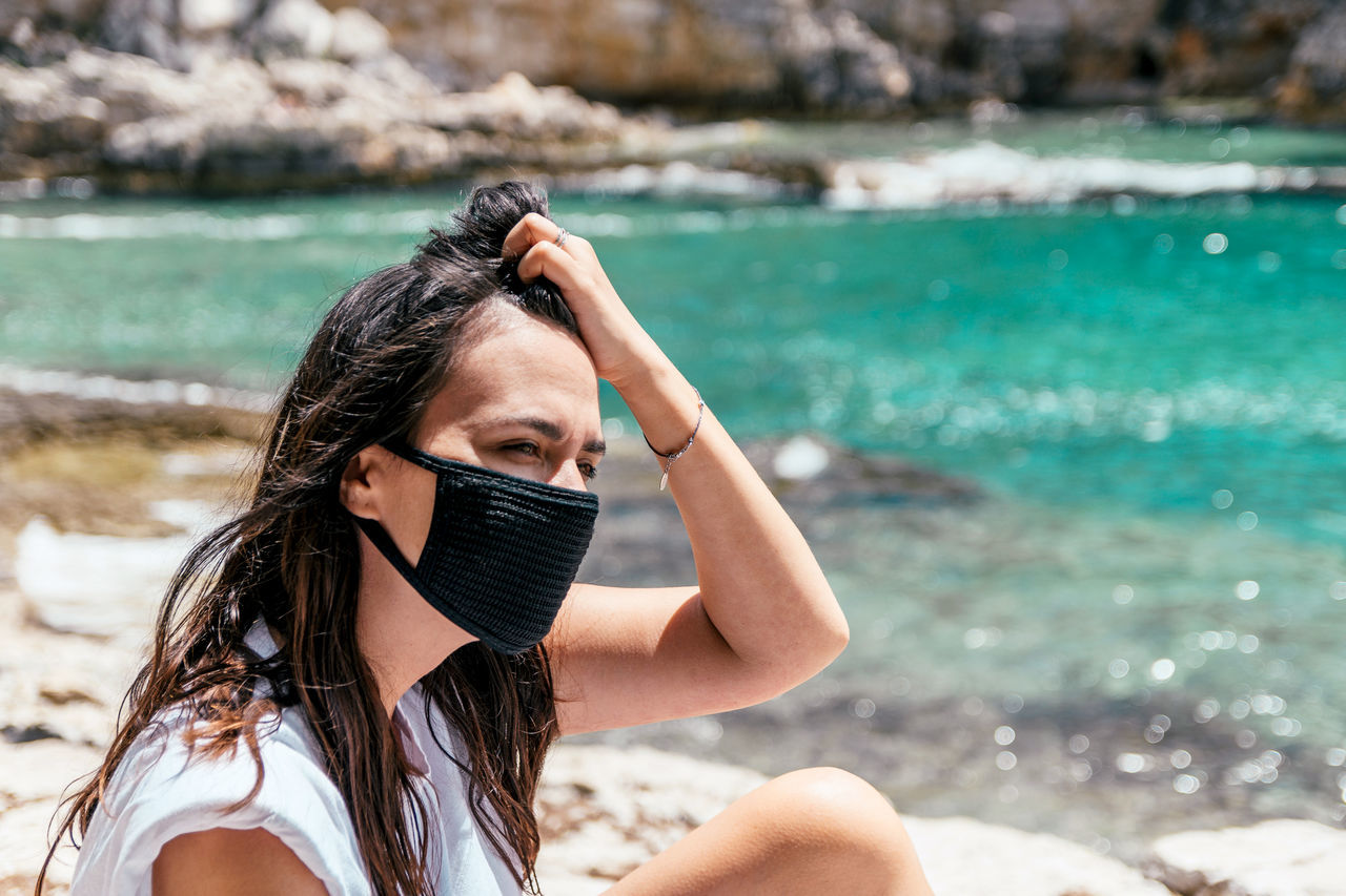 Portrait of a young woman wearing black protective mask on beach in summer. tourist, corona, covid.