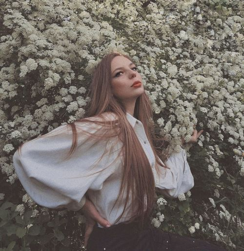 Portrait of young woman standing against blooming tree