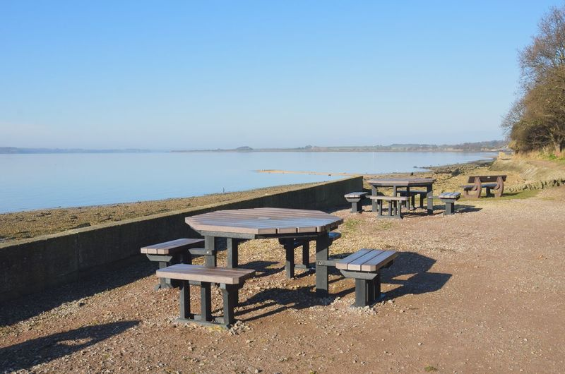 Empty coffee tables outside by coast Seat Bench Nature Outdoor Tables Tables And Chairs Table And Chairs At The Sea Coffee Tranquil Scene
