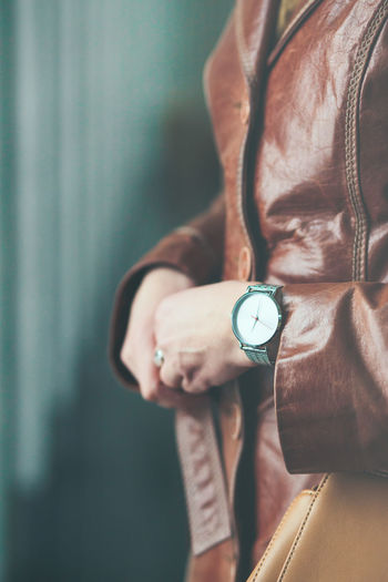 Midsection of woman wearing leather jacket and wristwatch while standing against blue wall