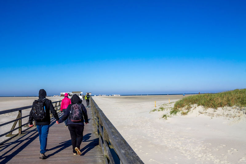 Rear View Of People Walking On Pier At Beach Against Clear Blue Sky During Sunny Day