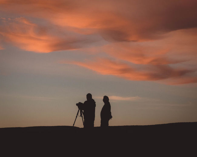 Silhouette people photographing on field during sunset