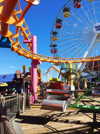 Amusement Park Santa Monica Pier Santa Monica California Roller Coaster Ferris Wheel Sky Outdoors Built Structure Low Angle View Multi Colored Day Architecture No People Blue Scenics Sunlight Colorful
