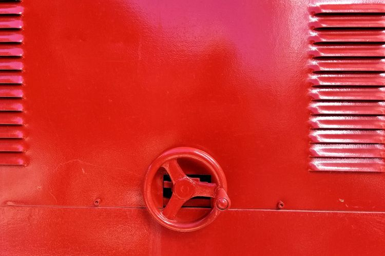 Close-up of red metallic wheel on wall