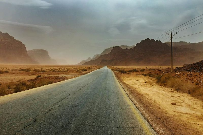 Empty country road with mountains in desert against sky