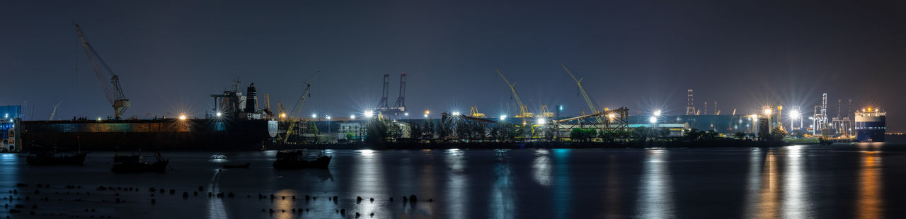 Illuminated commercial dock against sky at night