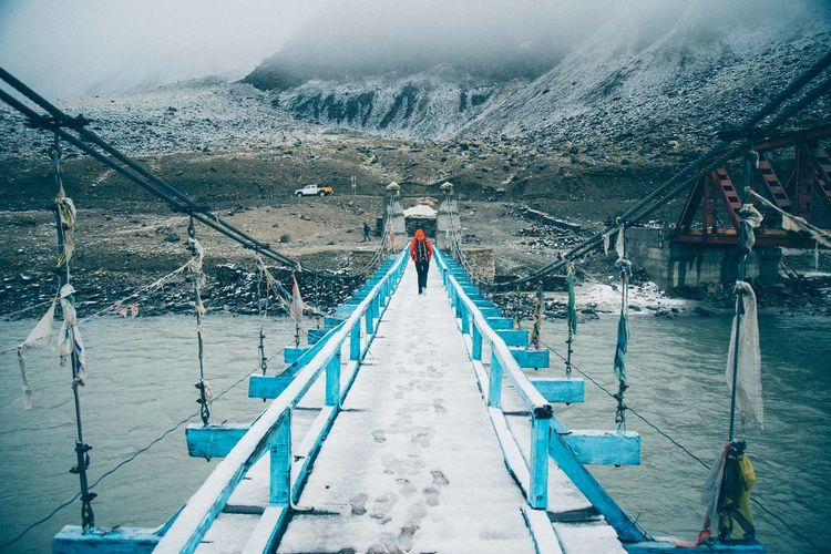 Walking alone on the snow bridge heading to Himalayan mountain Beauty In Nature Day Full Length Himalayas India Lake Leisure Activity Lifestyles Men Mountain Nature Person Pier Railing Rear View Scenics Sky The Way Forward Tranquility Water