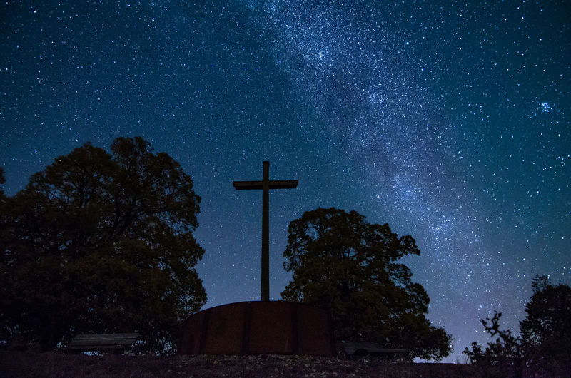 Low angle view of cross on tree against sky at night
