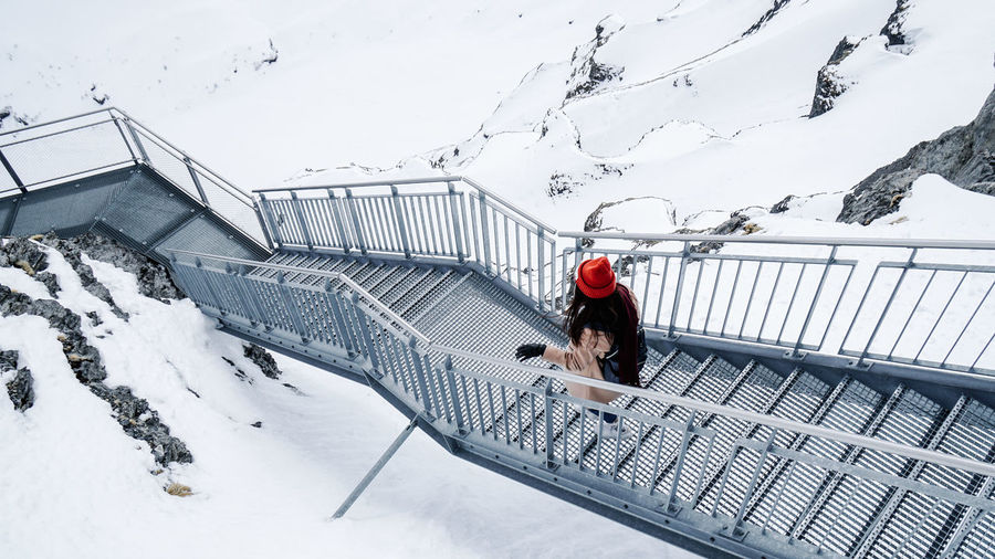 Architecture Built Structure Clothing Cold Temperature Covering Day Full Length Leisure Activity Lifestyles Mountain Nature One Person Outdoors Railing Real People Snow Snowcapped Mountain Warm Clothing White Color Winter Women