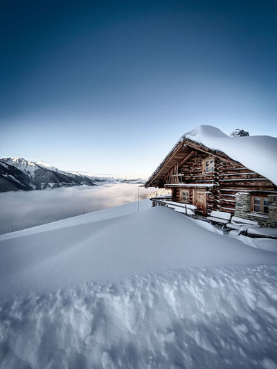 House on snowcapped mountain against sky at sunrise